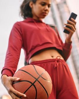 屋外でバスケットボールを保持し、彼女の電話をチェックしている女性