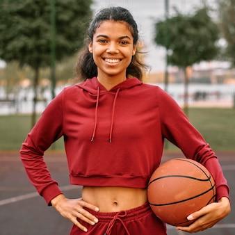 Женщина, держащая баскетбол на открытом воздухе