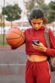 彼女の電話をチェックしながらバスケットボールを保持している女性