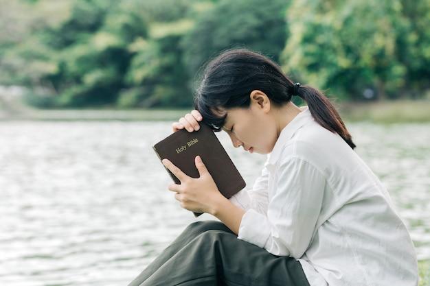 自然の背景である聖書を持っている女性は神に忠実であり、神の言葉を愛している