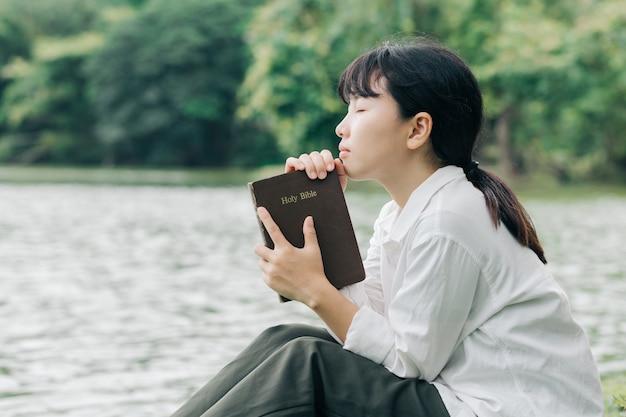 자연 배경 인 성경을 들고있는 여성은 하나님 께 충실하고 하나님의 말씀을 사랑합니다.