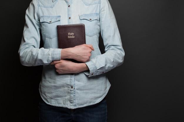 灰色の背景の上にカジュアルな服を着て手に聖書を持っている女性