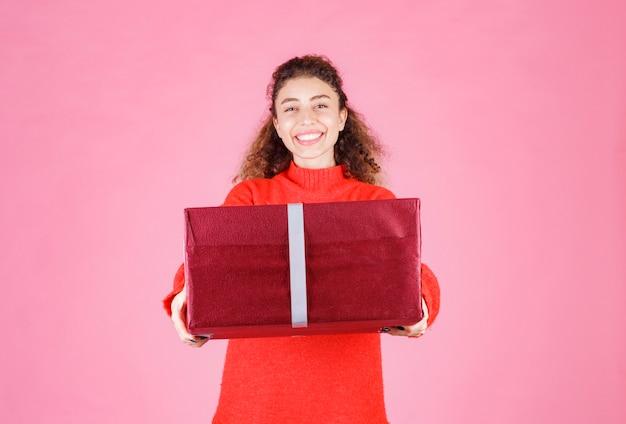 大きな赤いギフトボックスを持っている女性。