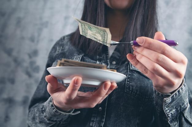 포크로 지폐를 들고 있는 여성