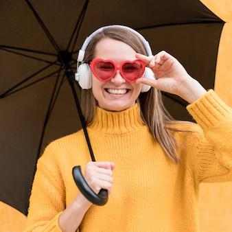 Женщина, держащая черный зонт при использовании наушников