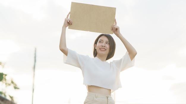 テキストに抗議するために空白のバナーを保持している女性。