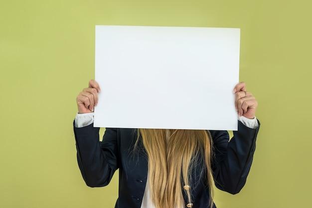 緑の背景に空白の看板を保持している女性