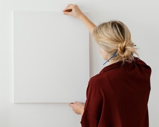 空白のキャンバスを保持している女性