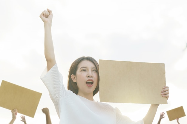 Женщина держит пустой плакат, чтобы выразить протест