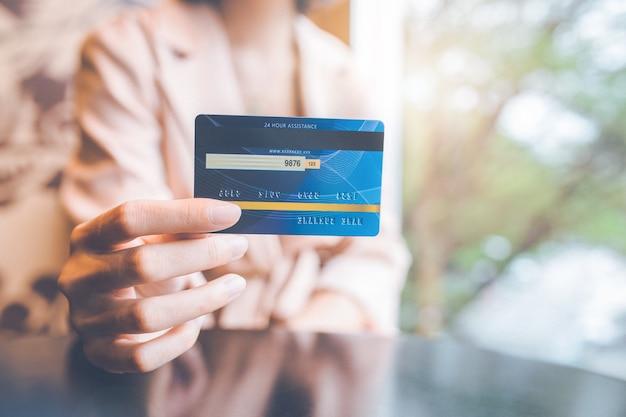 구매를 위해 파란색 신용 카드를 들고 있는 여자.