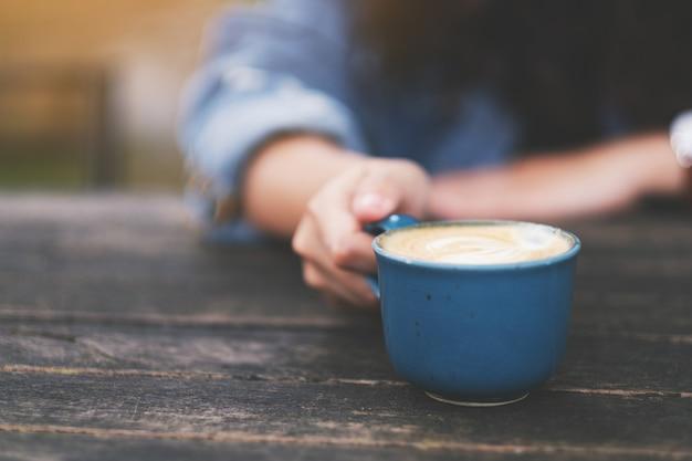 Женщина держит синюю чашку горячего кофе на деревянном столе