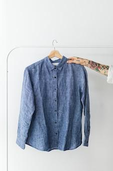 스튜디오에서 파란색 셔츠를 들고 있는 여자