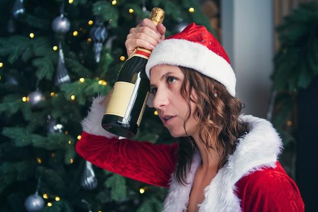 크리스마스 트리 배경에서 샴페인 한 병을 들고 있는 여자. 그의 머리를 잡아. 음주로 인한 두통. 휴가 후 숙취.