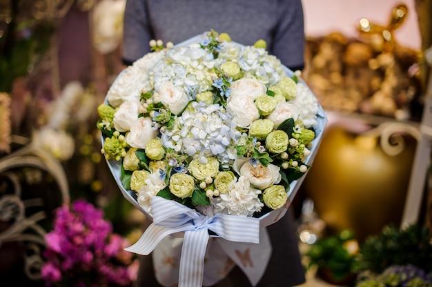 Женщина держит букет зеленых лютиков, белых пионов и других цветов
