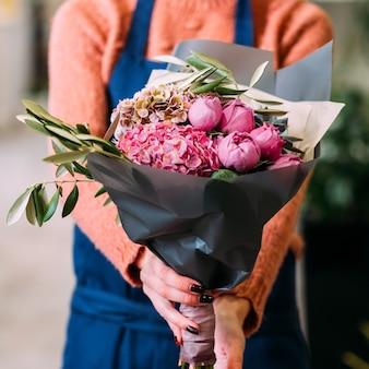 彼女が作ったクラフトラッピングで牡丹とアジサイの花束を持っている女性。小さな花のビジネスオーナー。女性のパワースタートアップの概念
