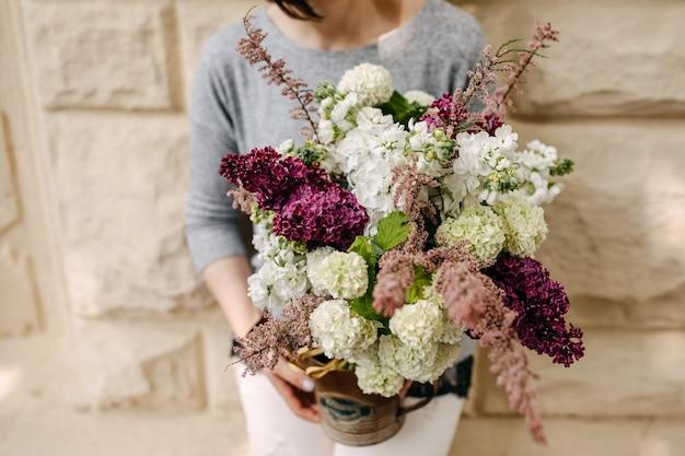 季節の花の花束を持っている女性