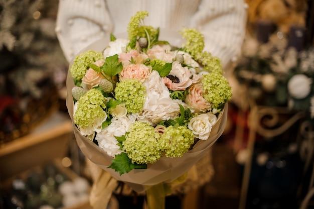 柔らかい緑のアジサイと白い花の花束を持っている女性