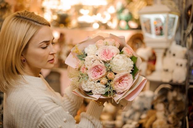 작은 가지와 녹색 잎으로 장식 된 부드러운 분홍색 모란 장미 꽃다발을 들고 여자