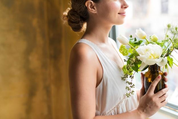 白い花の花束を持っている女性