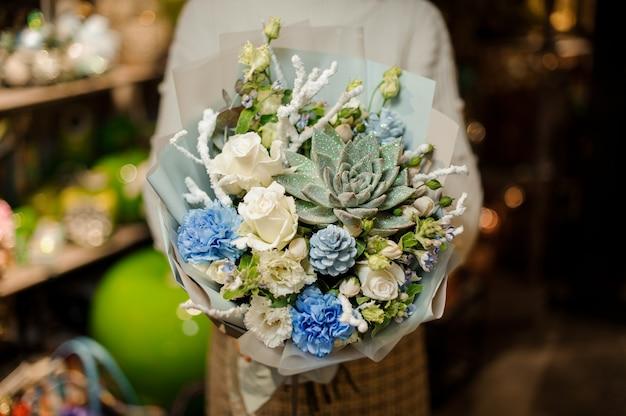 Женщина держит букет из белых роз, гвоздики, искусственных веток и суккулентов
