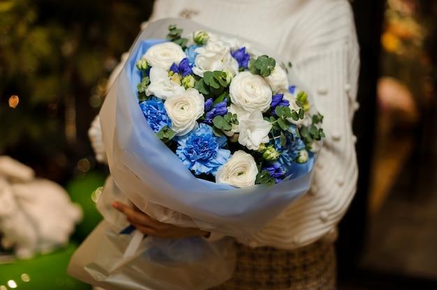 緑の葉で飾られたマットな透明な紙に包まれた青と白の花の花束を持っている女性