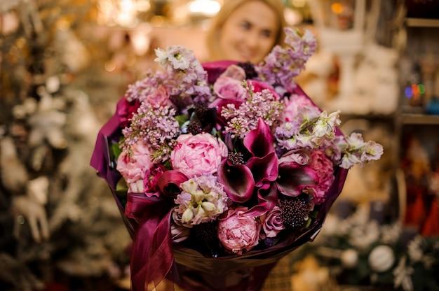 어두운 색 종이에 싸여 분홍색, 보라색, 진홍색 꽃과 꽃다발을 들고 여자