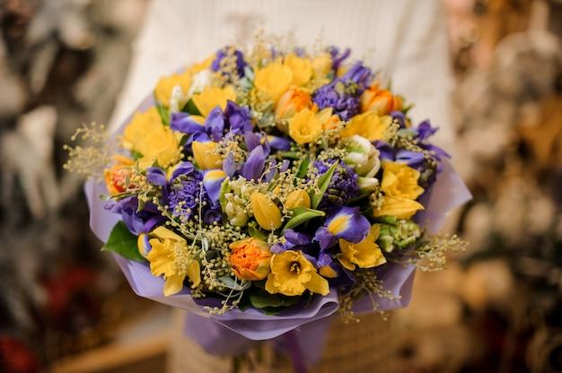 보라색 종이에 싸서 보라색과 노란색 꽃과 꽃다발을 들고 여자