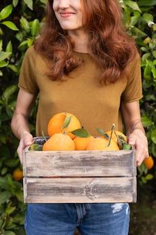 그녀의 손에 오렌지 가득 상자를 들고 여자