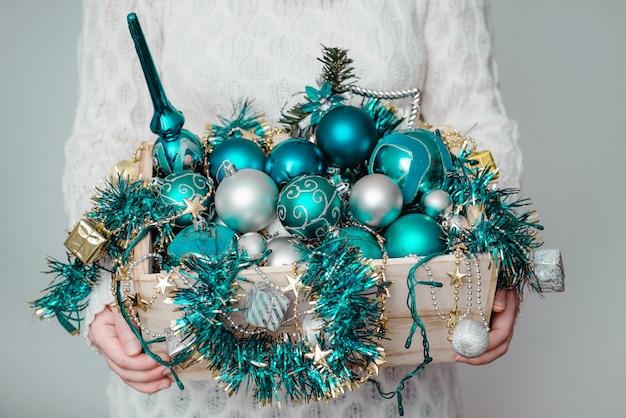 Женщина держит коробку синих рождественских украшений и гирлянд на серой стене