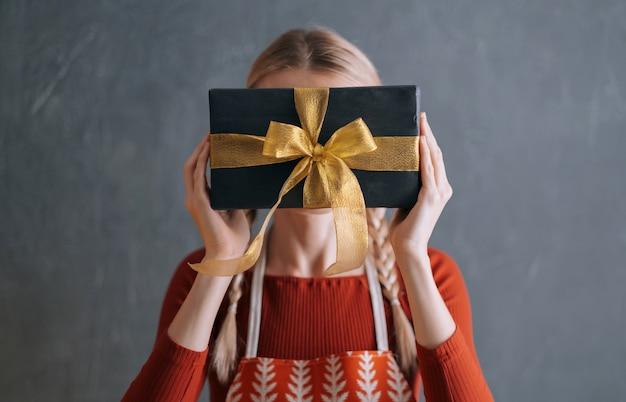 彼女の顔の前で彼女の手にクリスマスプレゼントの箱を持っている女性