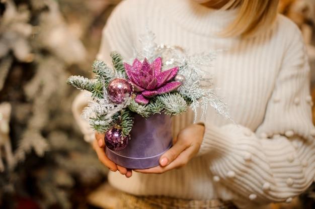 장신구와 전나무 나뭇 가지로 장식 된 분홍색 반짝이로 덮여 녹색 즙이 많은 상자를 들고 여자