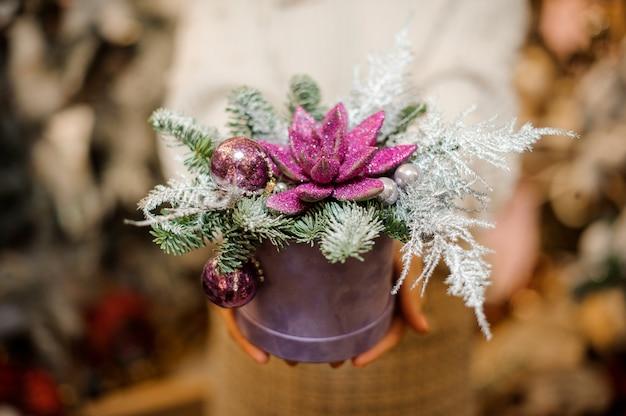 장식으로 장식 된 핑크색 반짝이로 덮여 녹색 즙이 많은 상자를 들고 여자