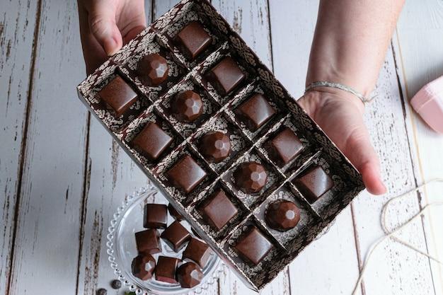 Женщина, держащая коричневую коробку шоколадных конфет.