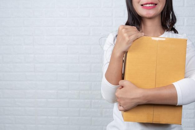 Женщина, держащая коричневый почтовый ящик сделанные жесты с языком жестов.