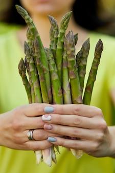Женщина держит в руках кучу зеленой спаржи на открытом воздухе, копья свежей зеленой спаржи на солнце, скопируйте пространство для текста. урожай, готово к приготовлению, здоровая веганская диета, местная еда.