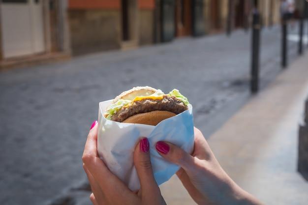 ハンバーガーを手に持った女性