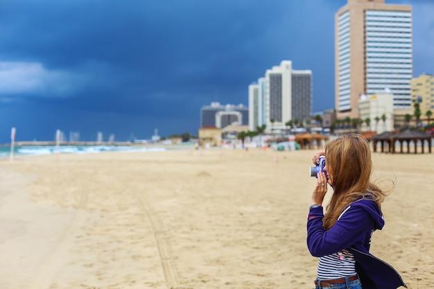도시와 호텔에 대 한 해변에서 카메라를 들고 여자.