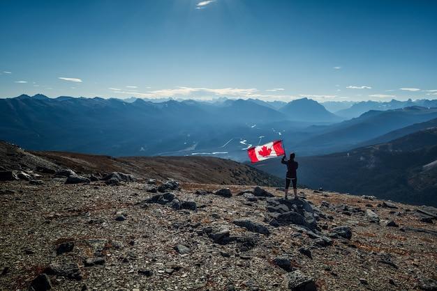 カナダ、アルバータ州ジャスパー国立公園のカナディアンロッキー山脈(ロッキー山脈)でカナダ国旗を掲げている女性。