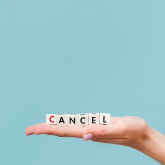 コピースペースを持つ小さなキューブから作られたキャンセルされたメッセージを保持している女性