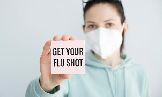 Get your flu shot、医療コンセプトでカードを持っている女性