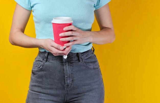 コーヒーの段ボールのカップを保持している女性