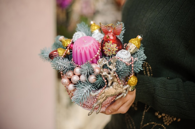 モミの木、カラフルなガラス玉、おもちゃで作られたクリスマスの組成を保持している女性