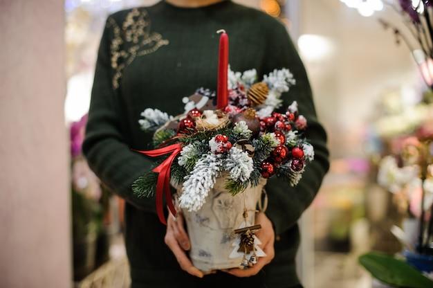 モミの木、ガラス玉、コーン、雪、キャンドルで作られたクリスマスの組成を保持している女性