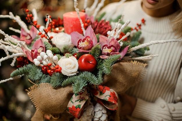 Женщина держит новогоднюю композицию с розовыми орхидеями, белыми розами, еловыми ветками, красным яблоком и свечой в мешковине в цветочном магазине