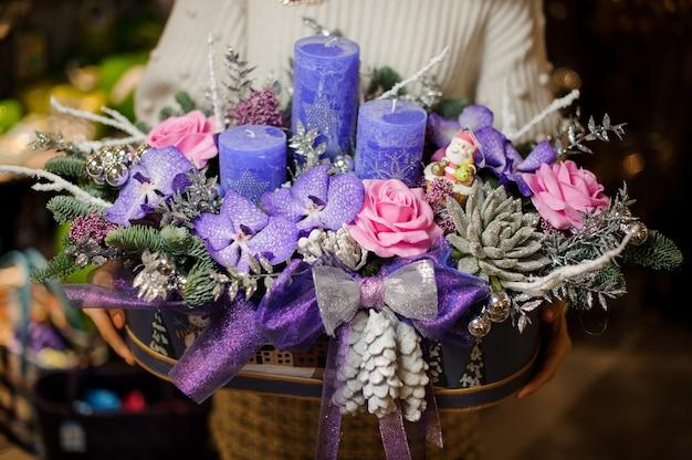 상자에 보라색과 분홍색 꽃, 다육 식물, 전나무 나뭇 가지와 촛불 크리스마스 구성을 들고 여자
