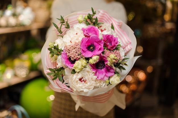 Женщина держит рождественскую композицию с фиолетовыми розовыми и белыми пионовидными розами, украшенными зелеными листьями