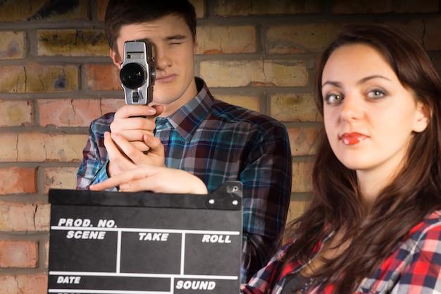 彼女の後ろのビデオグラファーがアクションを開始して撮影または記録を開始する準備ができているカチンコを持っている女性、レトロなカメラを持っている若い男性