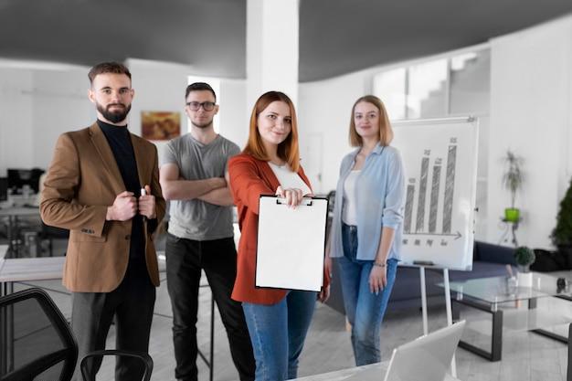 Женщина держит буфер обмена рядом со своими коллегами