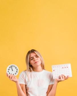 Женщина держит часы и менструальный календарь копией пространства