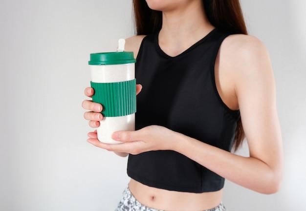 운동 여자 배경으로 손에 커피 컵을 들고 여자.
